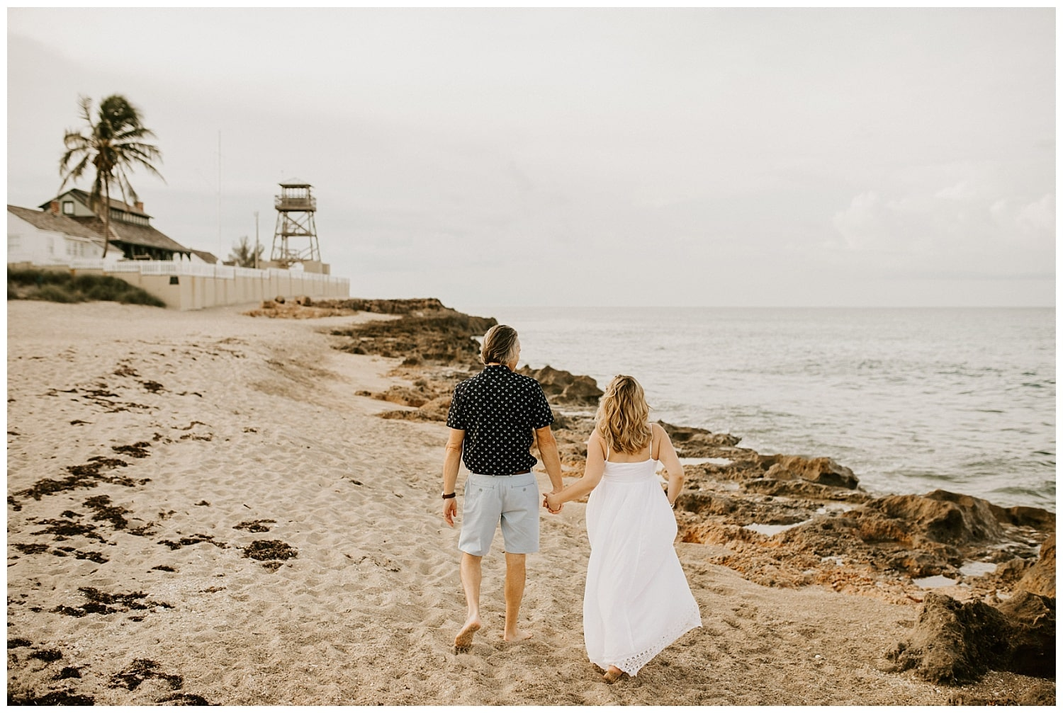 couple walking on the beach holding hands at the house of refuge