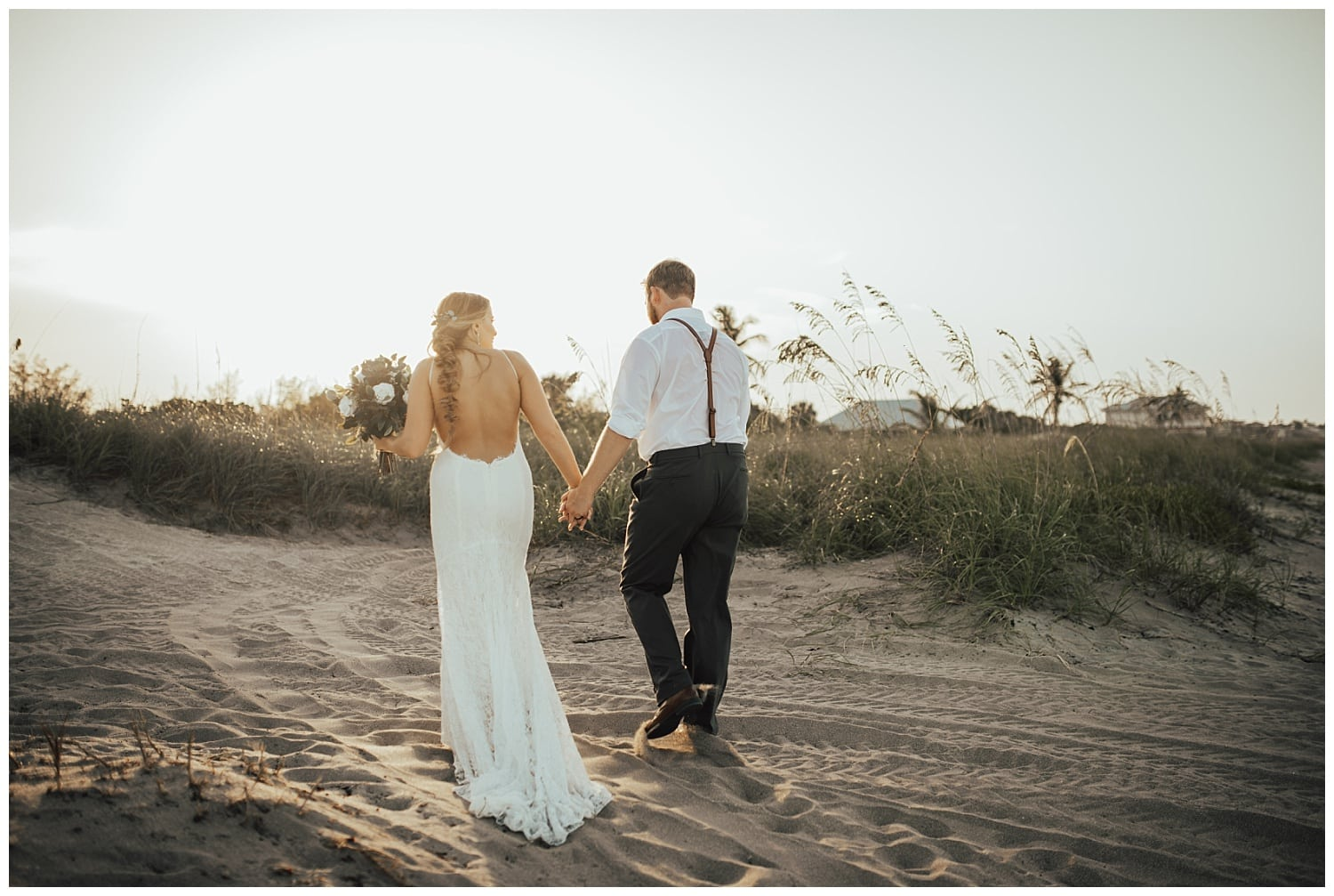 bride and groom holding hands at the beach
