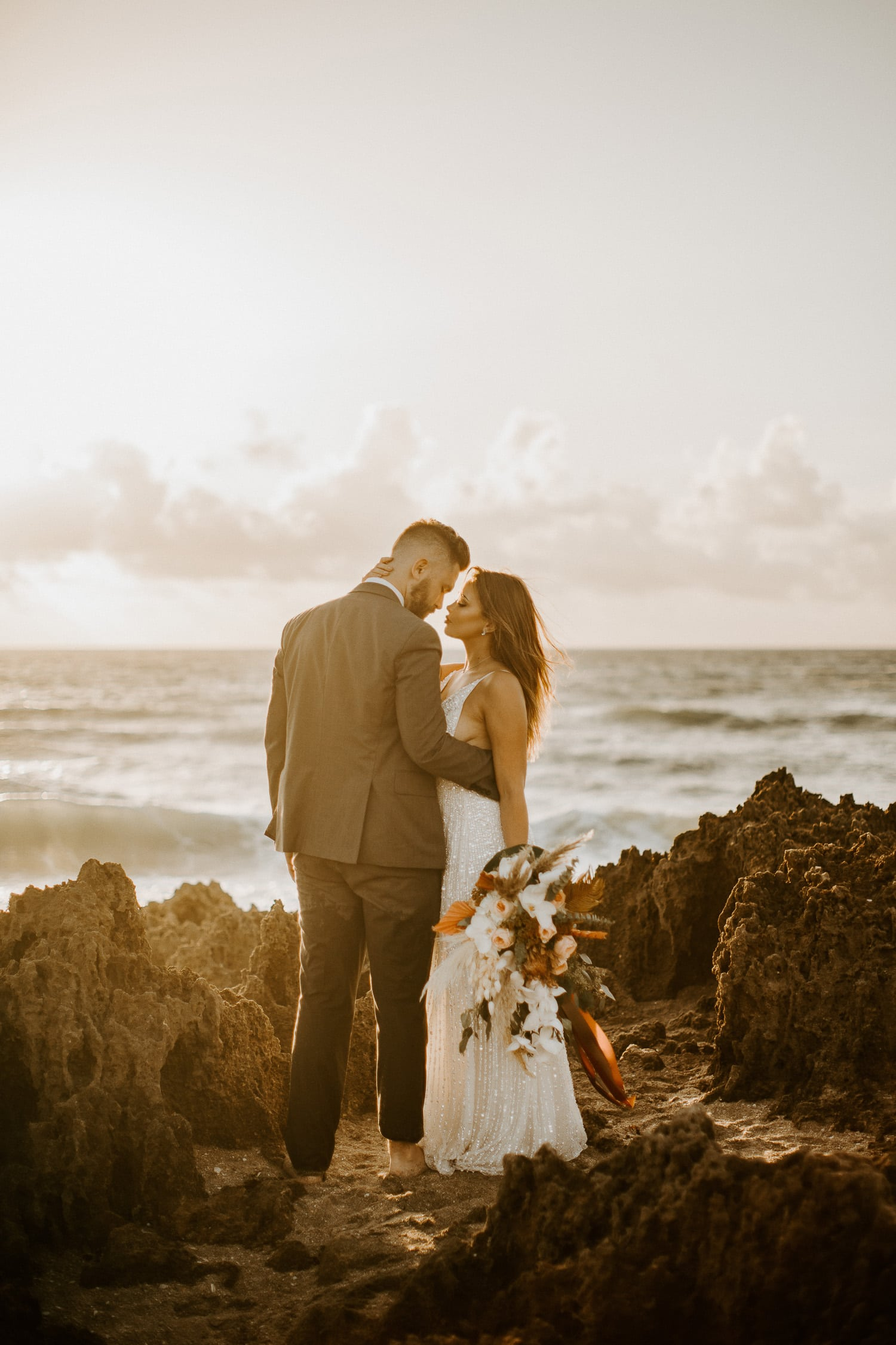Bride and groom standing on rocks on the beach at the House of Refuge, which is one of the best places to elope in Florida.