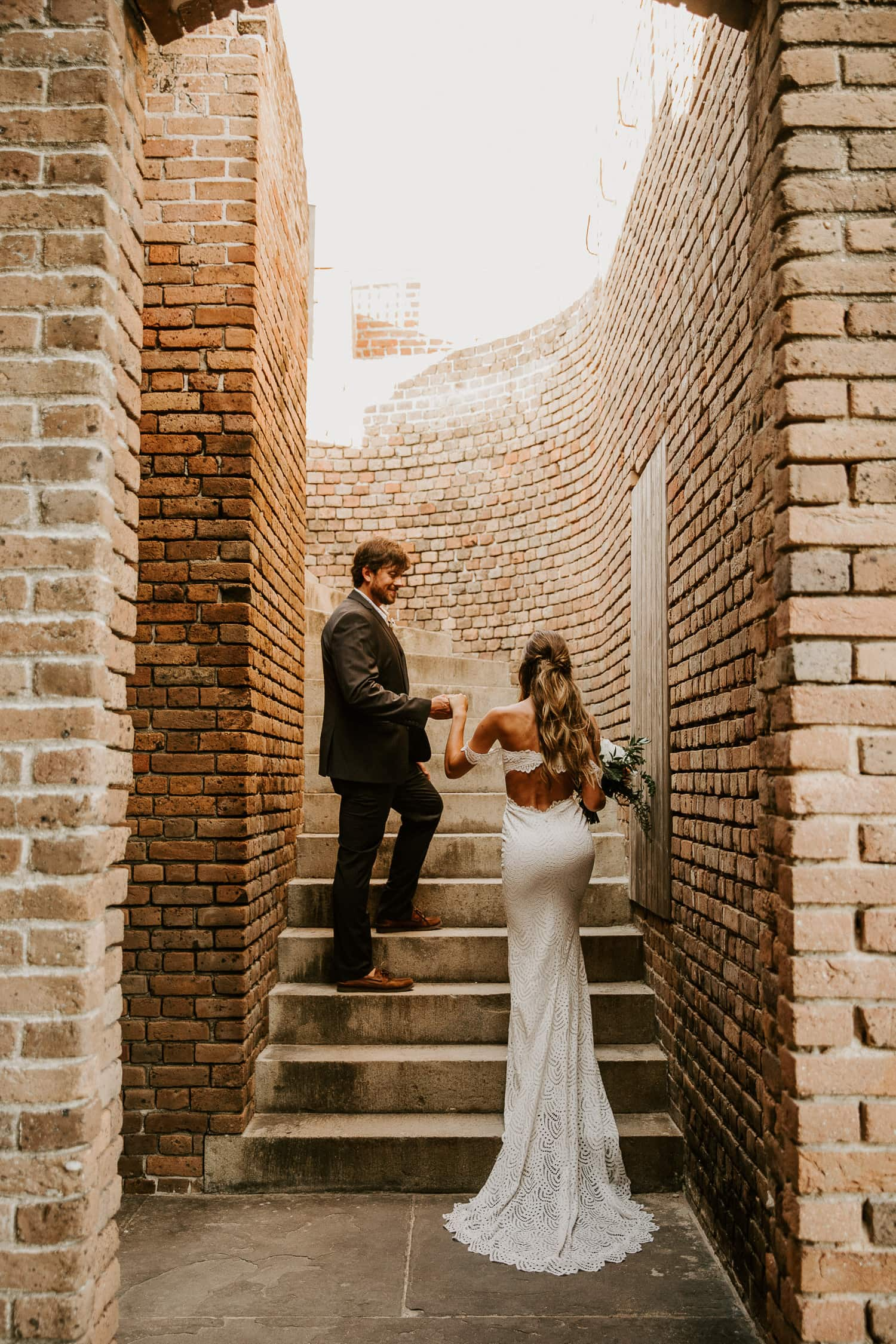 Bride and groom walking up a brick staircase at Fort Zachary Taylor, which is one of the best places to elope in Florida.