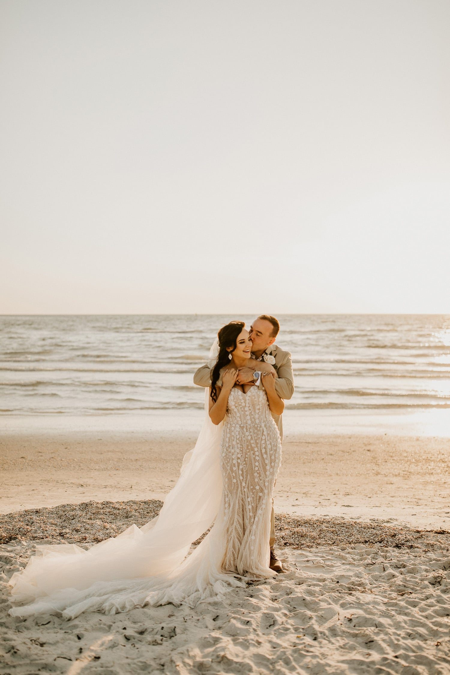 Bride and groom laughing on the beach together at Pass-a-Grille Beach in St. Pete, a perfect place to elope in Florida at sunset.