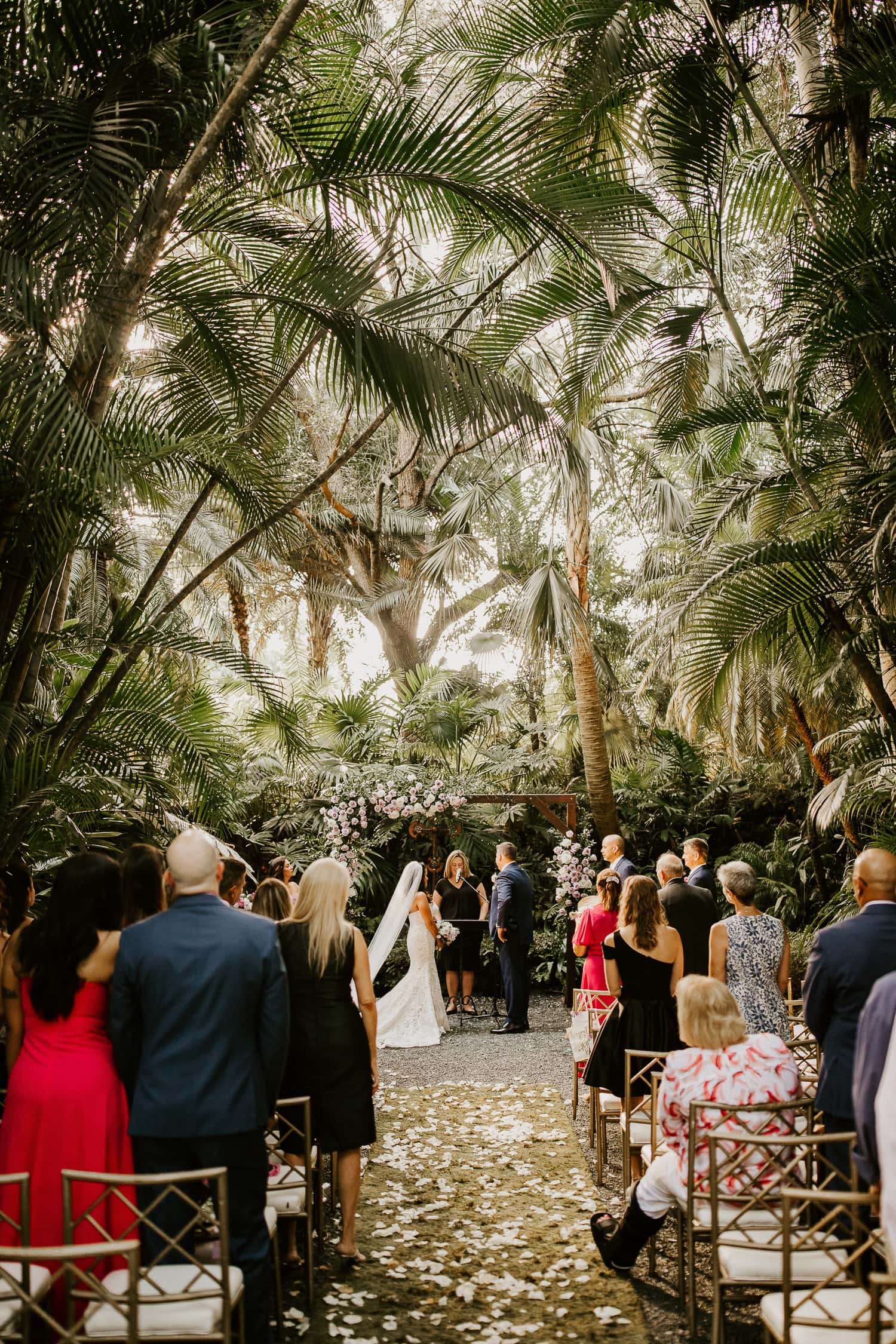 Wedding ceremony under palm trees at the Cooper Estate in South Florida.