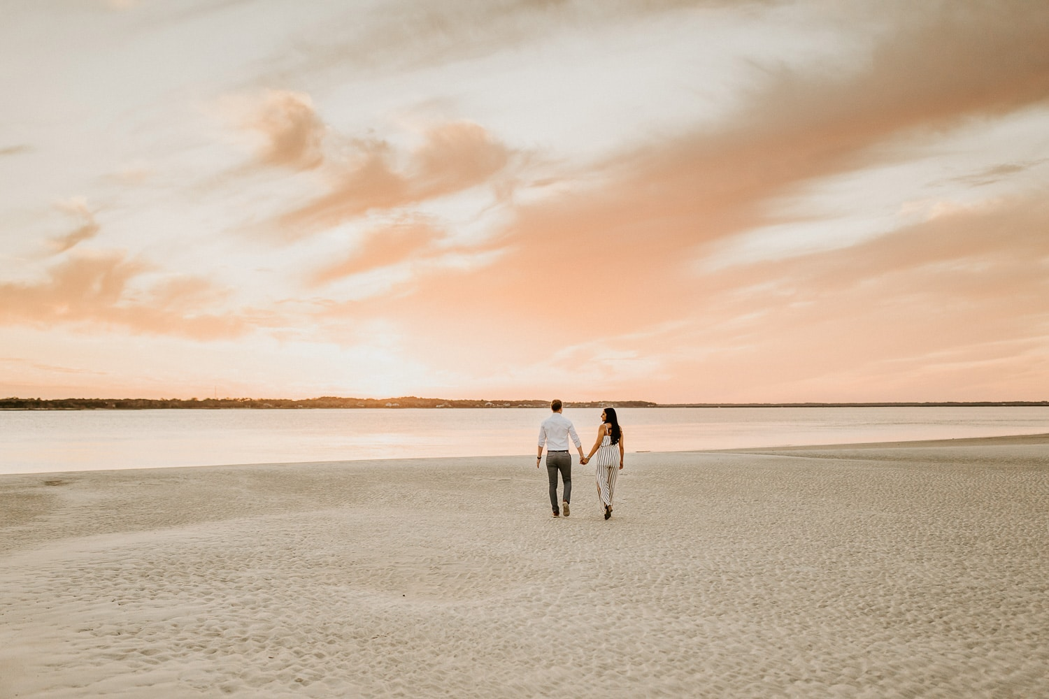 A couple is holding hands walking on the beach at sunset at Amelia Island State Park. Find elopement packages below.