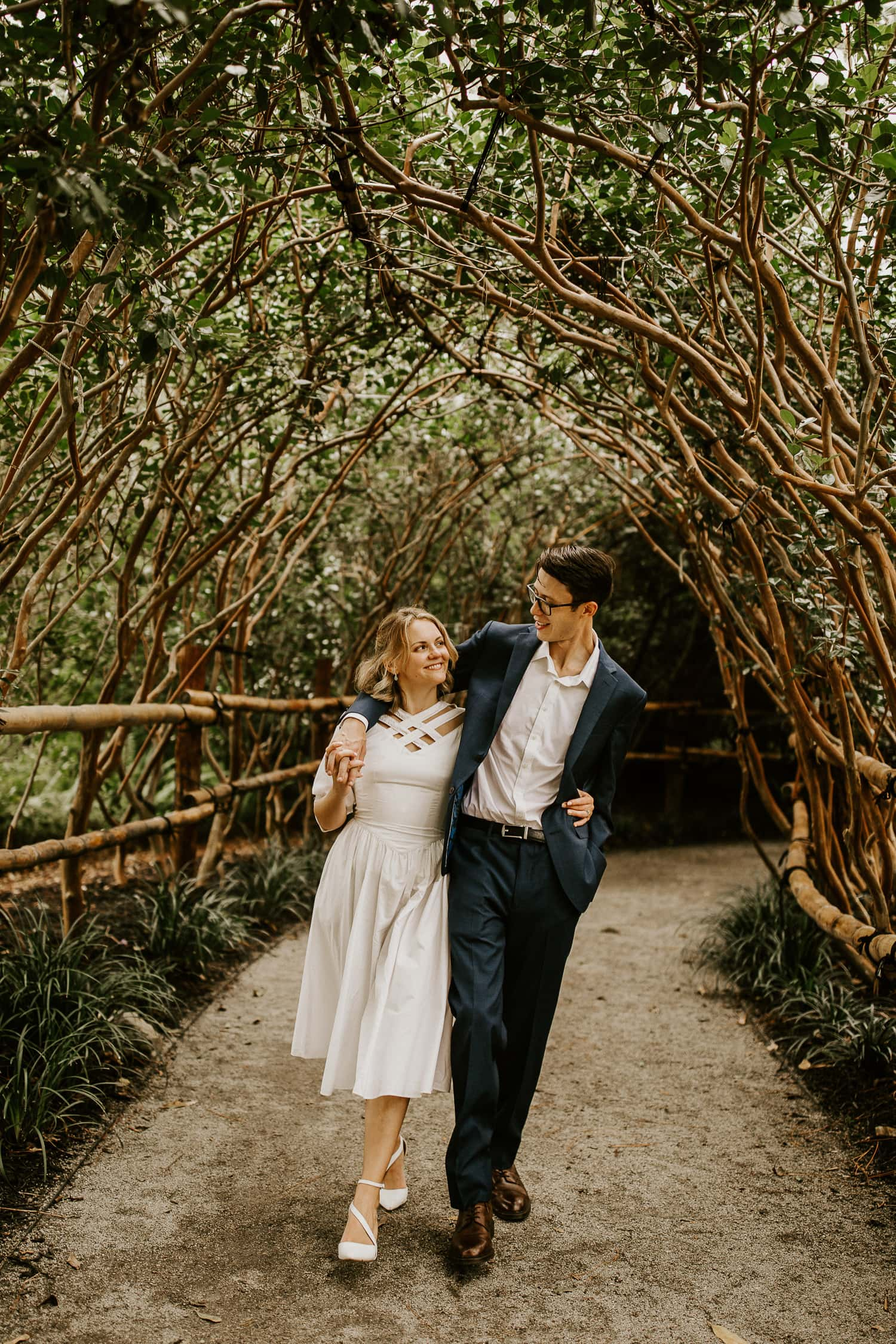 Bride and groom walking together under tree tunnel in Morikami Gardens, one of the most unique places to elope in Florida.