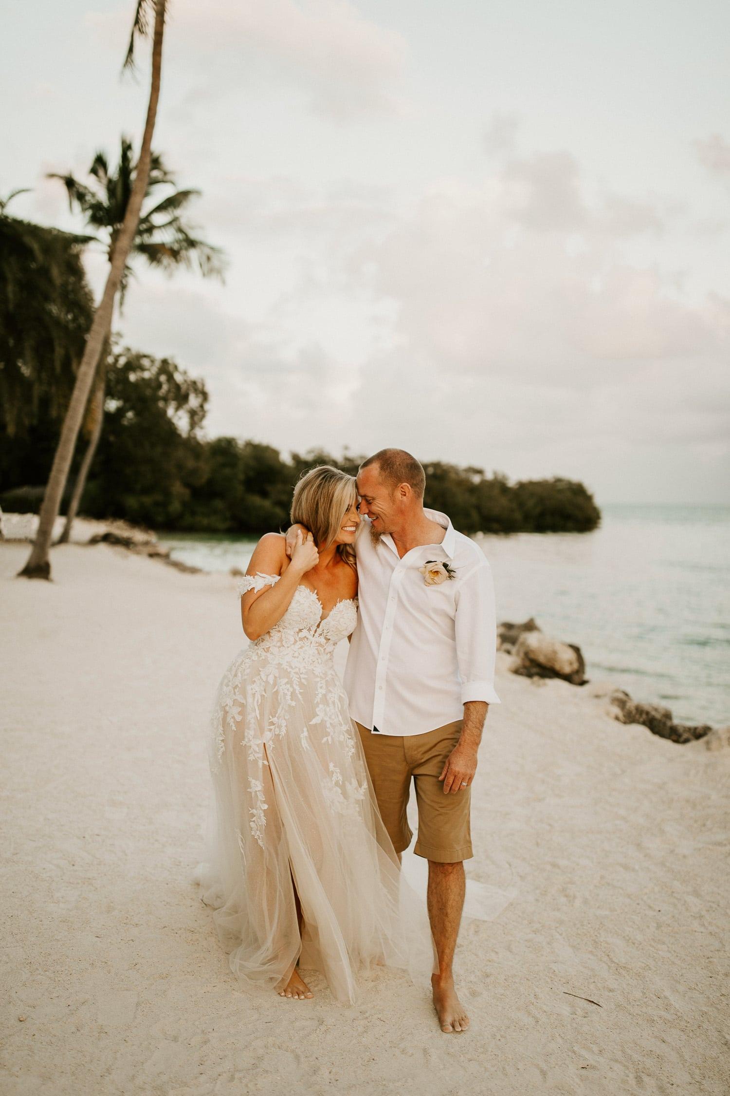 Bride and groom walking together along the beach at Pelican Cove Resort in Islamorada, Florida.