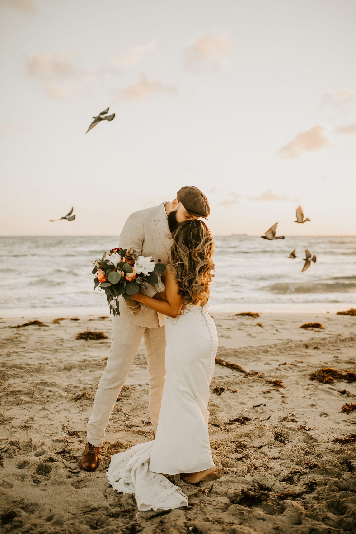Bride and groom are kissing on South Pointe beach with birds flying behind them.