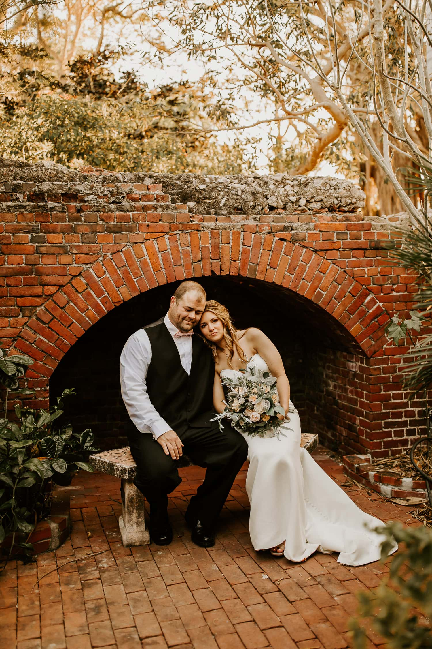 Bride and groom sitting on a bench under a brick archway in West Martello Gardens in Key West, one of the most beautiful places to elope in Florida.