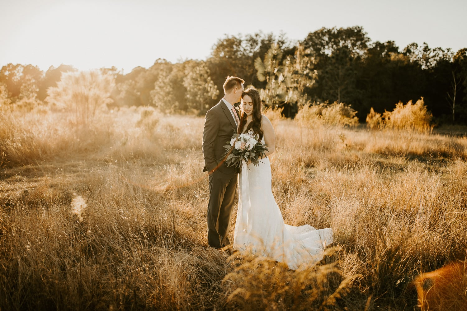 Bride and groom standing together in a field of golden grass at Lake Louisa State Park.
