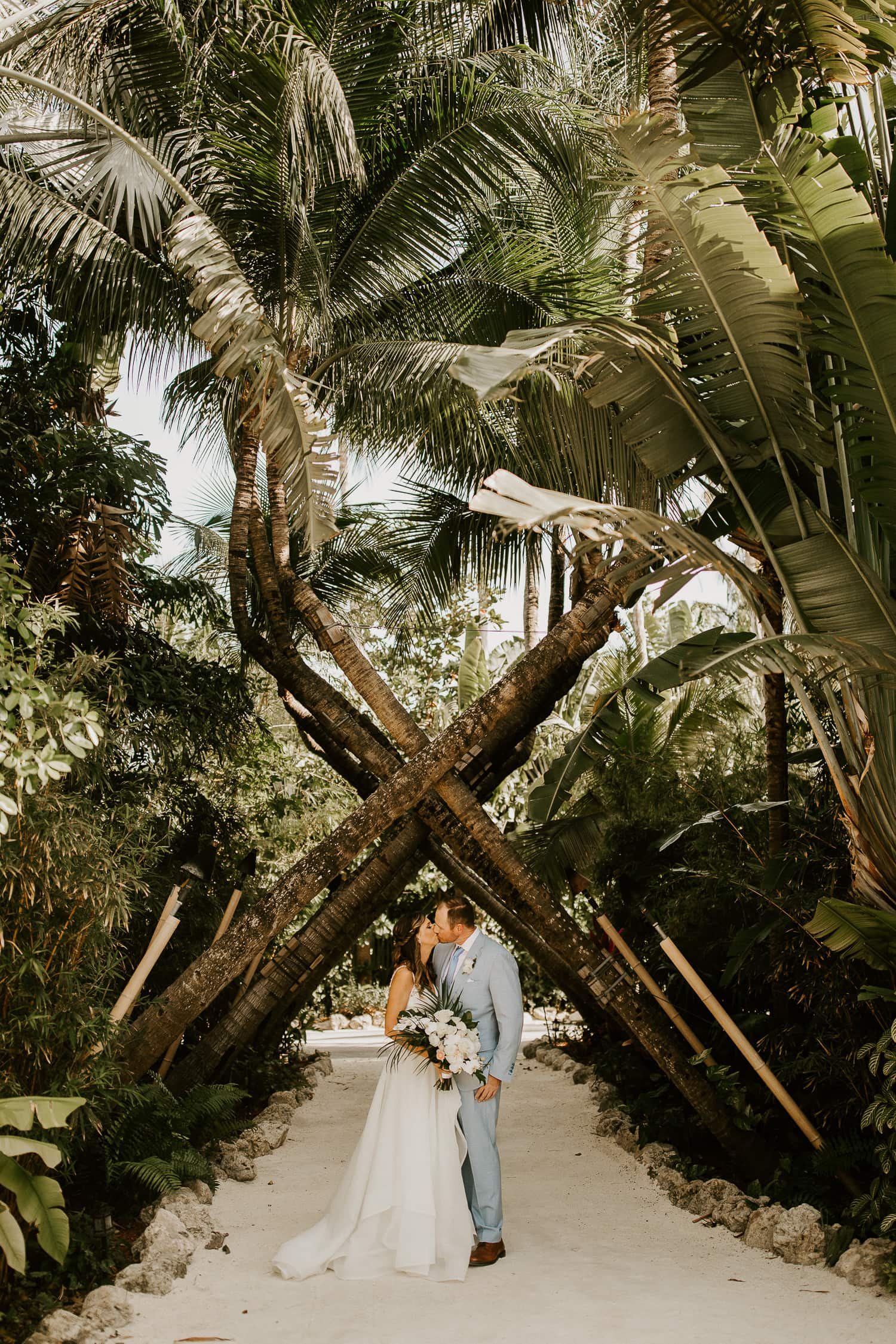 Bride and groom kissing under palm trees at Cheece Lodge and Spa in the Florida Keys.