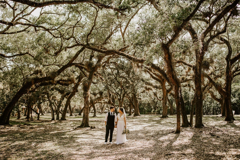 Bride and groom holding hands under large oak trees at Matheson Hammock Park.